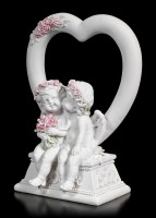 Zwei weiße Cherubim Figuren vor Herz