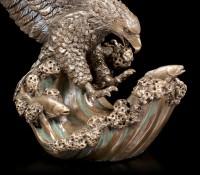 Adler Figur fängt Fisch aus dem Wasser