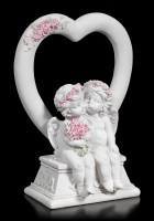 Two white Cherubim Figurines in front of a Heart