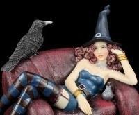 Hexen Figur mit Rabe sitzt auf Sofa