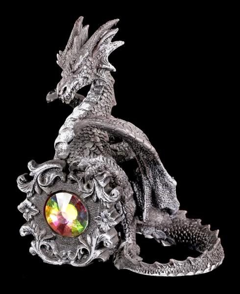Black Dragon Figurine sitting behind a Crystal