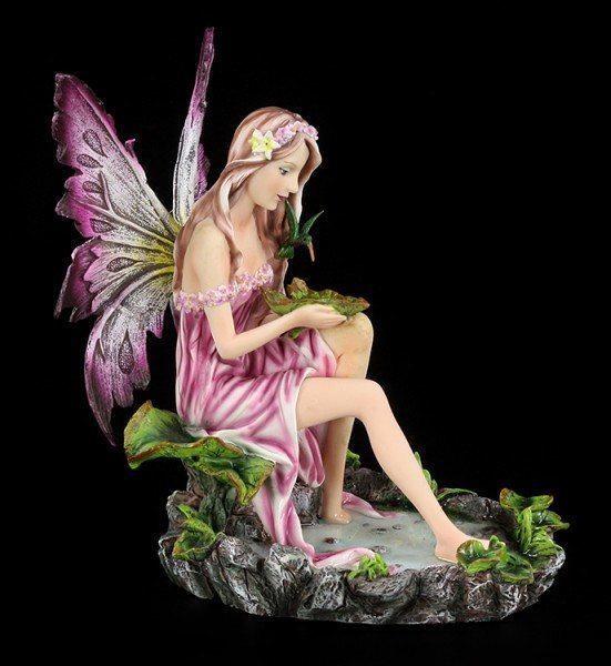 Elfen Figur sitzt an Teich mit Kolibri