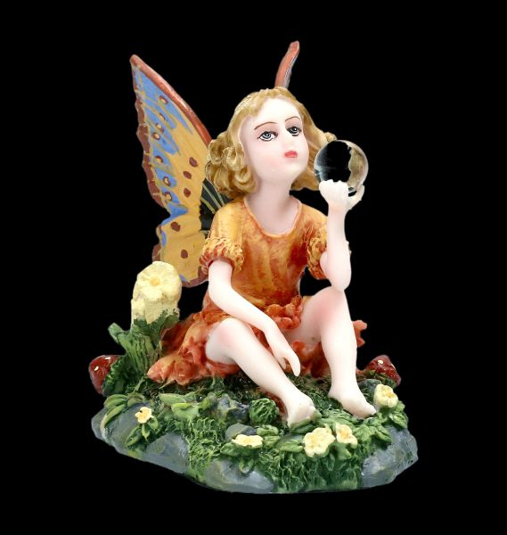 Small Fairy Figurine sitting on a Flowers Meadow