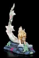 Mermaid Figurine reads Lost Books