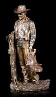 Cowboy Figur mit Sattel am Baumstumpf