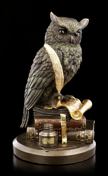 Eulen Figur auf Büchern mit goldener Feder