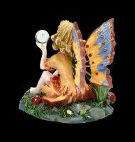 Kleine Elfen Figur sitzt in Blumenwiese