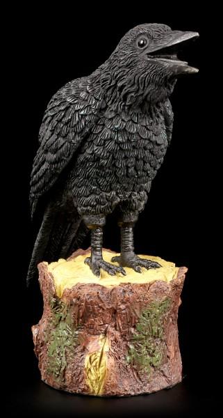 Ravens Figurine standing on Tree Stump