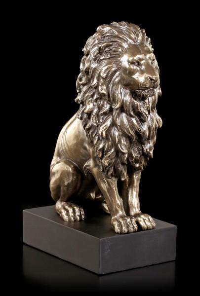 Sitzende Löwen Figur auf schwarzem Monolith