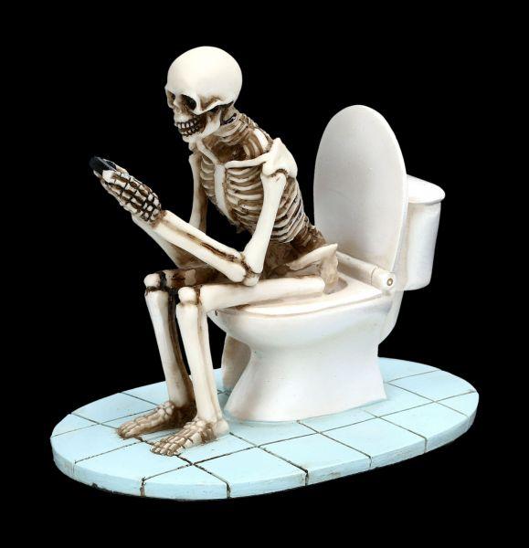 Skelett Figur sitzt auf WC