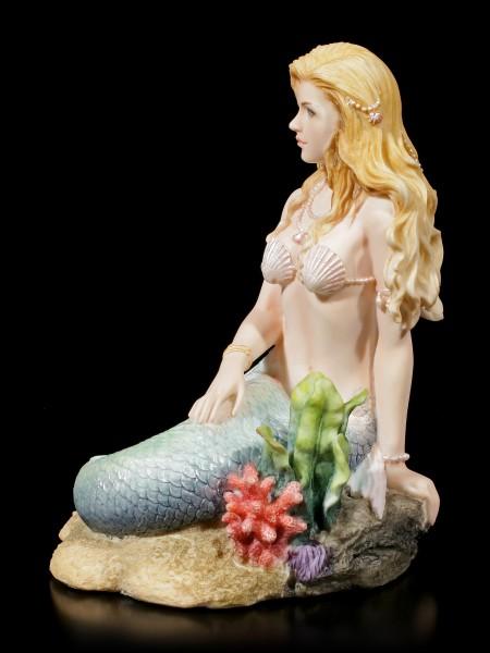 Meerjungfrauen Figur sitzt am Meeresgrund